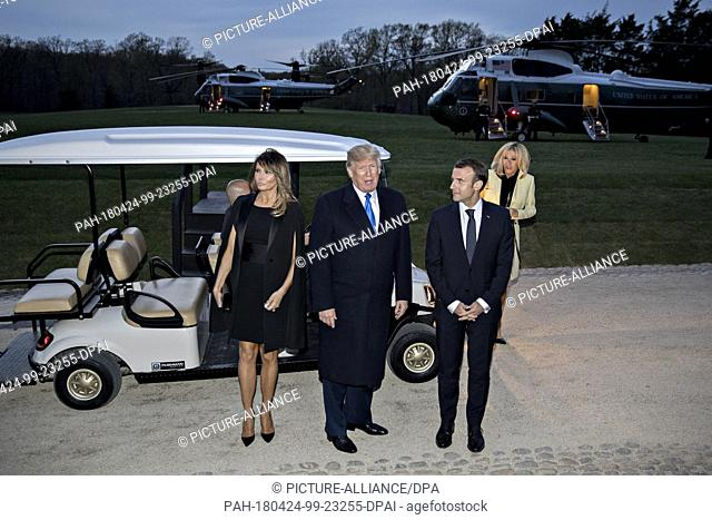 U.S. President Donald Trump speaks to members of the media next to a golf cart following a dinner with Emmanuel Macron, France's president, right, and U