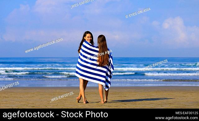 Smiling woman looking over shoulder while standing with female friend in towel at beach
