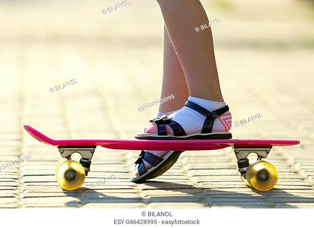 Child slim legs in white socks and black sandals on plastic pink skateboard on bright sunny summer blurred copy space pavement background