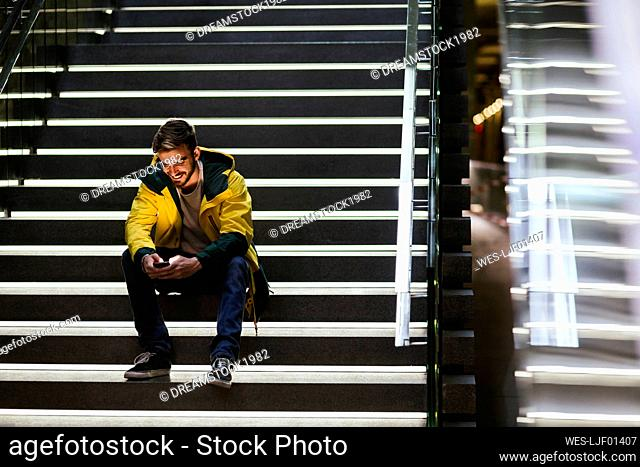 Smiling man sitting on stairs in subway station using cell phone