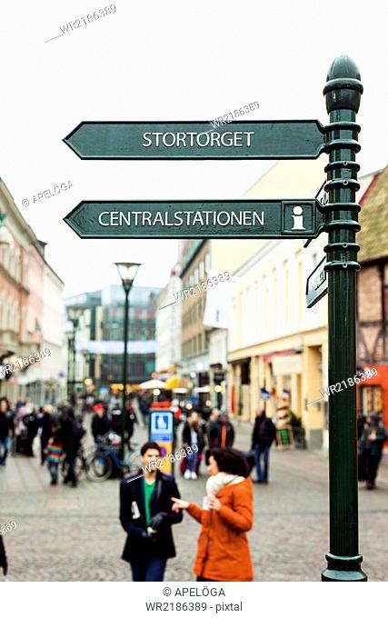 Sign post above friends walking on street
