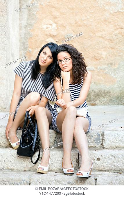 Two attractive young women are relaxing on a staircase after a night out