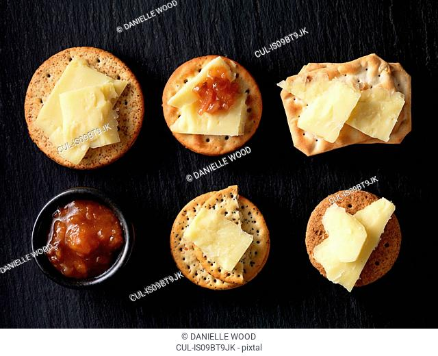 Still life of variety of cheese crackers with cheddar cheese and chutney on black slate, overhead view