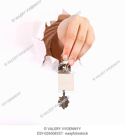 hand holds the keychain through a hole in a sheet of paper