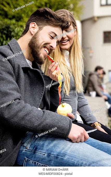 Young woman fedding her boyfriend with peel of an apple