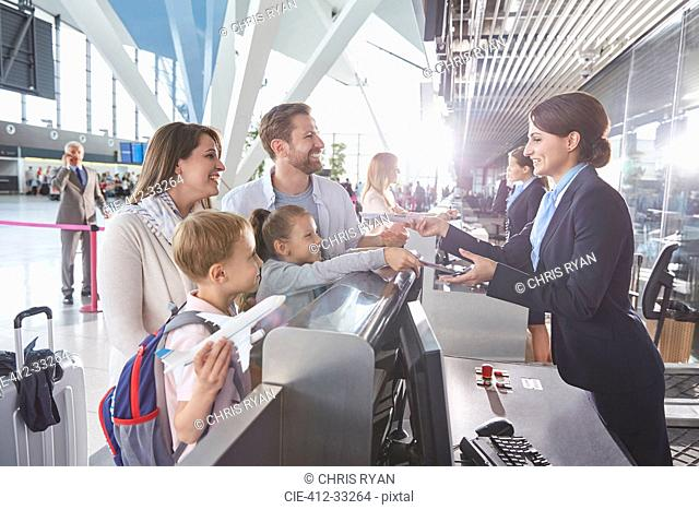 Customer service representative checking family tickets at airport check-in counter