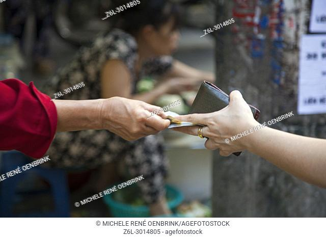 Paying for food at the street market in Hanoi, Vietnam