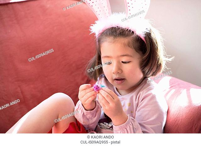 Young girl wearing bunny ears, looking at fluffy Easter chick