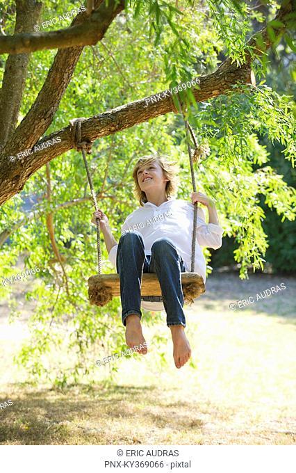 Happy little boy swinging on tree
