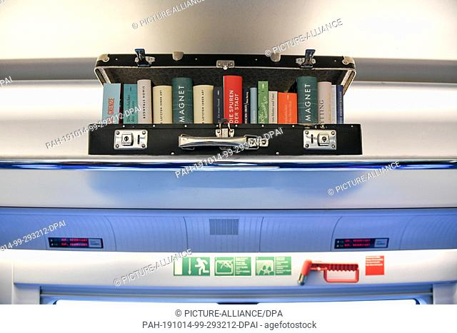 14 October 2019, Berlin: Books can be seen in the literature train on its way from Berlin to Cologne in a suitcase lying on the luggage rack