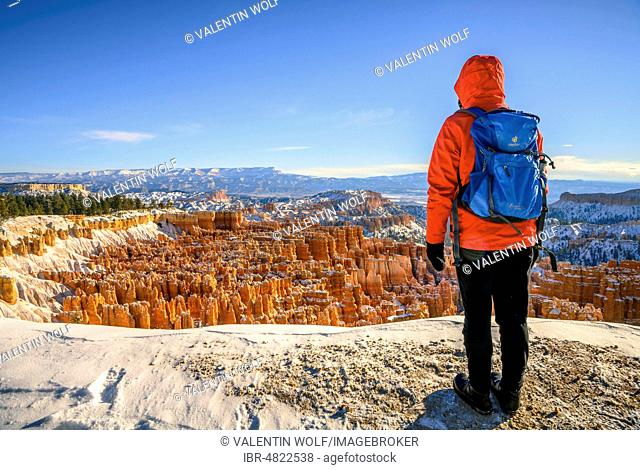 Young woman looking at the amphitheatre at morning light, bizarre snowy rocky landscape with Hoodoos in winter, Sunset Point, Bryce Canyon National Park, Utah