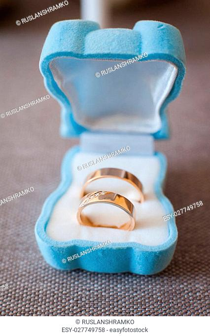pair of wedding rings with bokeh background blue box