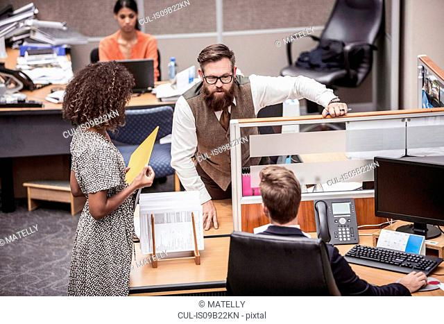 Businesswoman and men talking at office desk