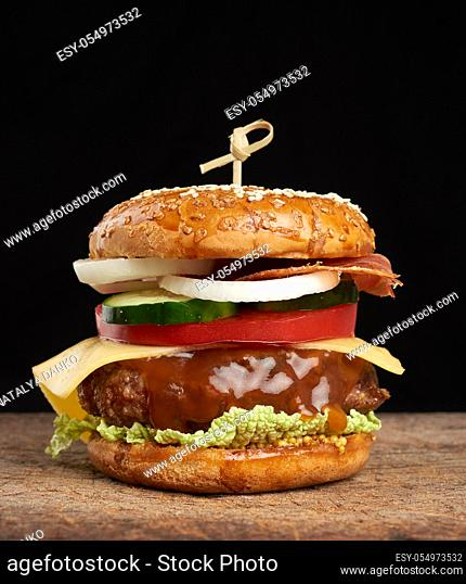 cheeseburger with tomatoes, onions, barbecue cutlet and sesame bun on an old wooden cutting board, black background. Fast food