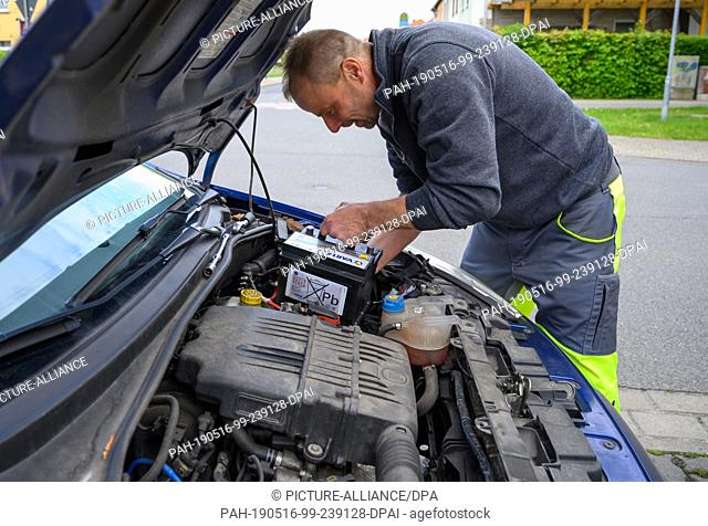 03 May 2019, Lower Saxony, Wolfenbüttel: Christian Müller, breakdown assistant at the ADAC, is installing a new Varta car battery in a car