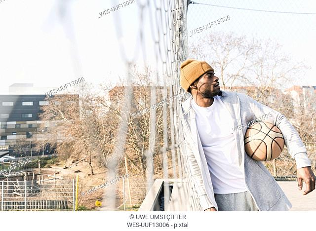 Basketball player on court leaning against fence