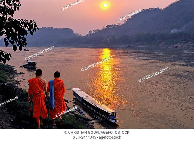 monks at sunset on Mekong River at Luang Prabang, Laos, Southeast Asia