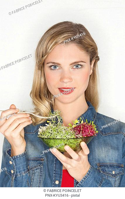 Portrait of a beautiful woman eating bean sprout
