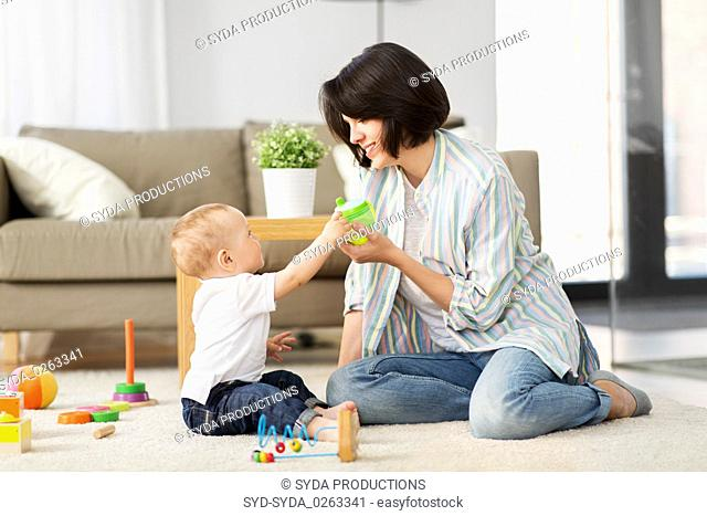 happy mother giving sippy cup to baby son at home