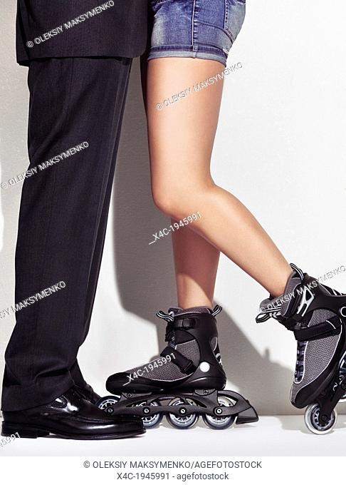 Closeup of legs of a man in a business suit and a young woman wearing inline skates standing together