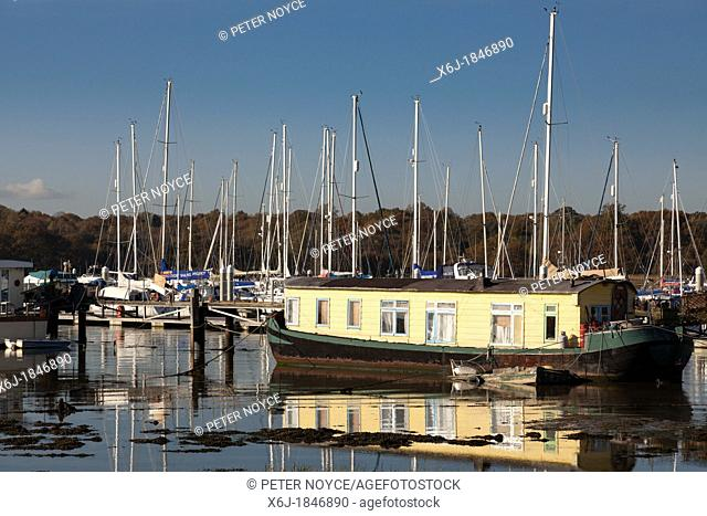 Houseboat moored in a marina on the River Hamble in winter sunshine