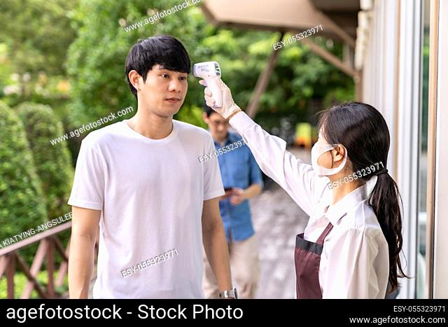 Asian waitress with face mask taking temperature to customer before getting in restaurant with social distance queue in line