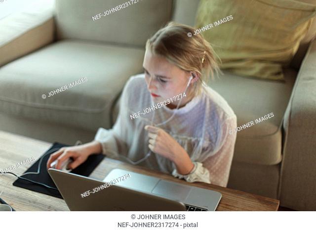 Teenage girl using laptop in living room