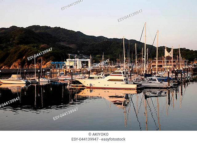 View of sail boats and yachts in small port at sunset, Japan