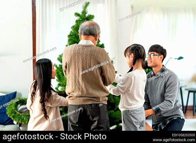 Multigenerational asian Family decorating a Christmas tree. Mom Dad daughter girl and grandfather decorate the Christmas tree prepare for season greeting of...