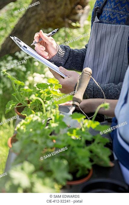 Close up plant nursery workers with clipboard and potted herbs