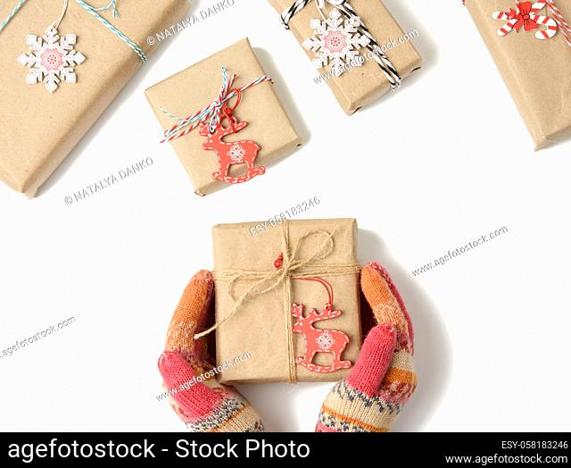 female hands in knitted mittens hold a box wrapped in brown paper and tied with a rope on a white background, top view