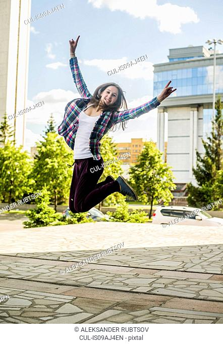 Young woman jumping mid air in city