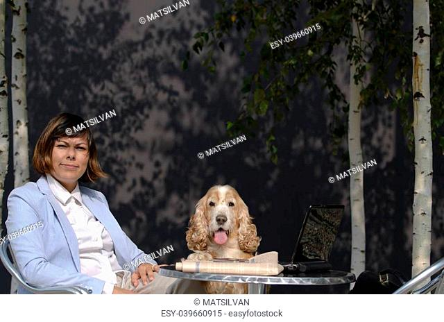 Business woman sitting down with her personal computer and her dog