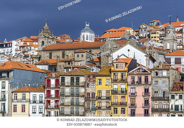 Row of buildings on the Douro riverfront in Porto city, Portugal. View with Parish Church of Saint Nicholas and Saint Francis Church