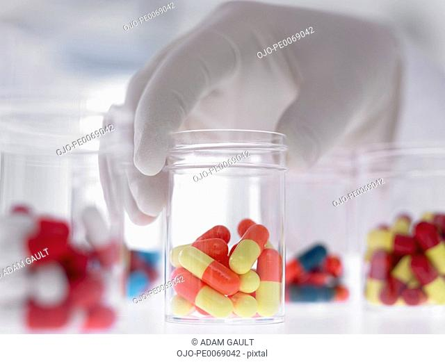 Scientist holding jar with capsules