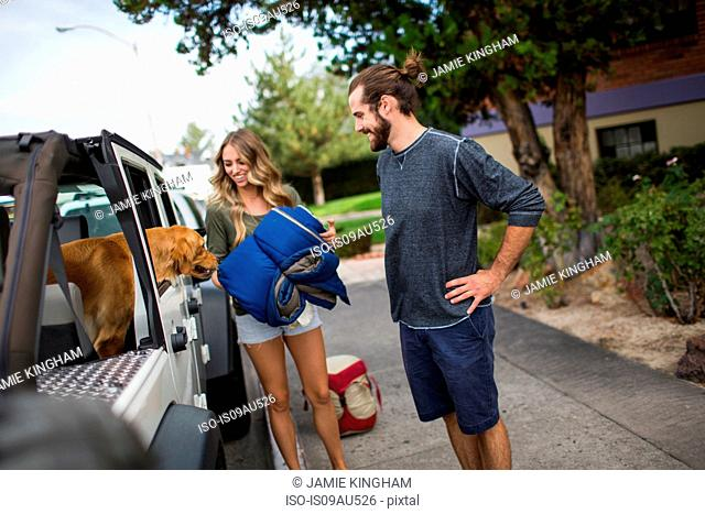 Young couple and dog preparing to load jeep for road trip
