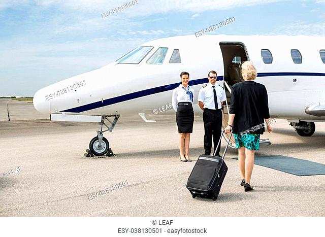 Rear view of businesswoman with luggage walking towards private jet while pilot and airhostess standing by
