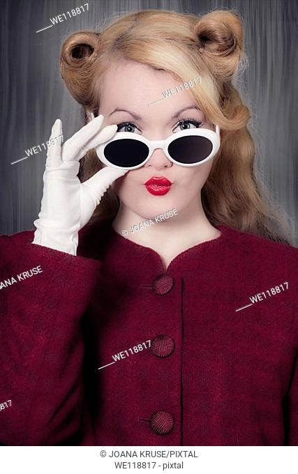 a woman in a vintage blazer with vintage sunglasses in 50s style, her mouth forming kissing lips