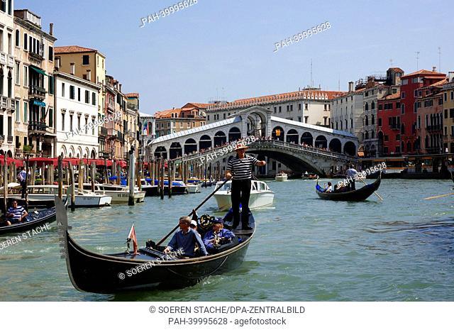 Gondolas and tourist boats travel on the Canal Grande near the Rialto Bridge in Venice, Italy, 3 May 2013. Photo: Soeren Stache | usage worldwide