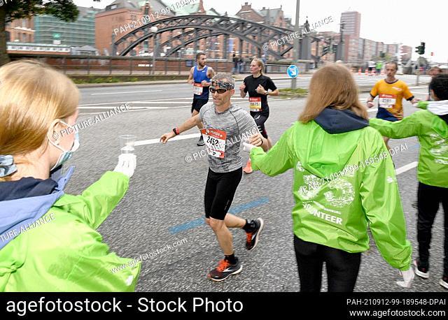 12 September 2021, Hamburg: Athletics: Marathon: Marathon runners at the water supply point in the Speicherstadt. Photo: Michael Schwartz/dpa