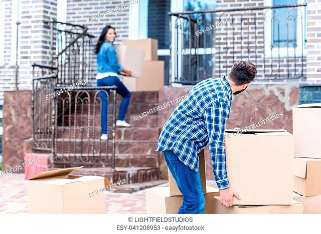 beautiful couple with boxes moving into new house