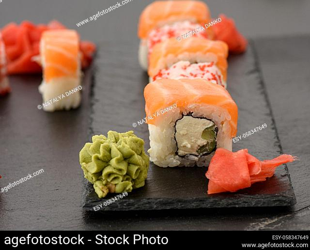 california sushi with red tobiko caviar and slices of philadelphia sushi on black slate board, close up