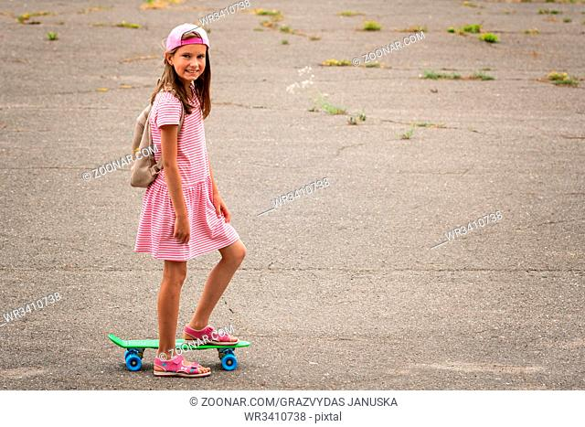 Urban girl ride with penny skateboard on asphalt street