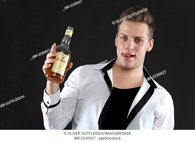 Young man holding a bottle of whiskey