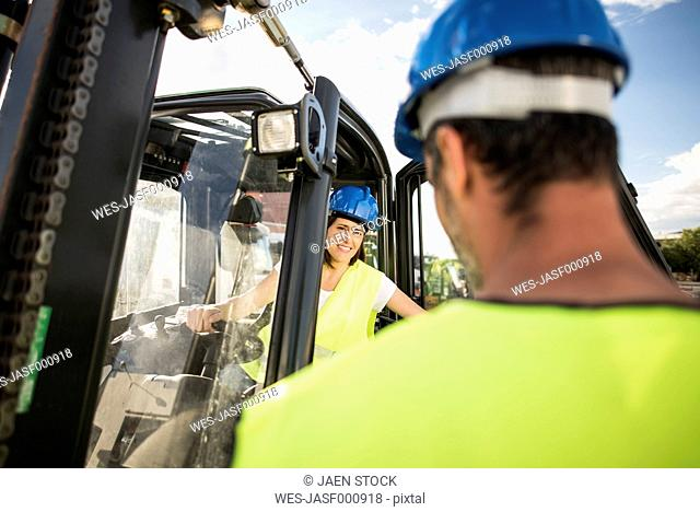 Woman in forklift talking to foreman of construction company