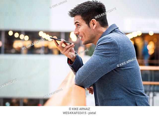 Businessman in lobby of a modern building, using smartphone