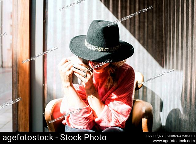 woman sat hiding behind a hat drinking coffee in a cafe in fall