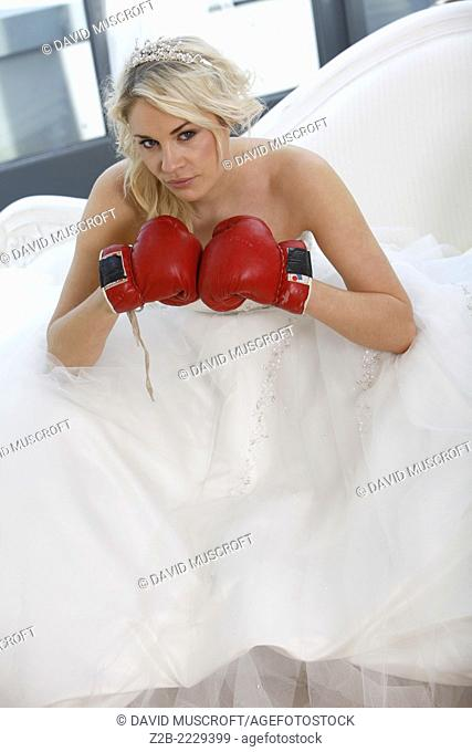 Wedding dress worn by a model as she wears boxing gloves