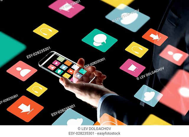 business, multimedia, people and modern technology concept - close up of businessman hand with transparent smartphone with menu icons on screen over black...