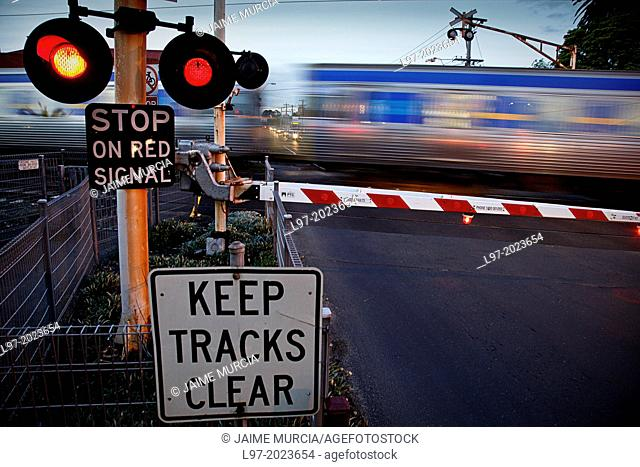 Passenger train moving rapidly through railway crossing with warning lights flashing, Melbourne Australia